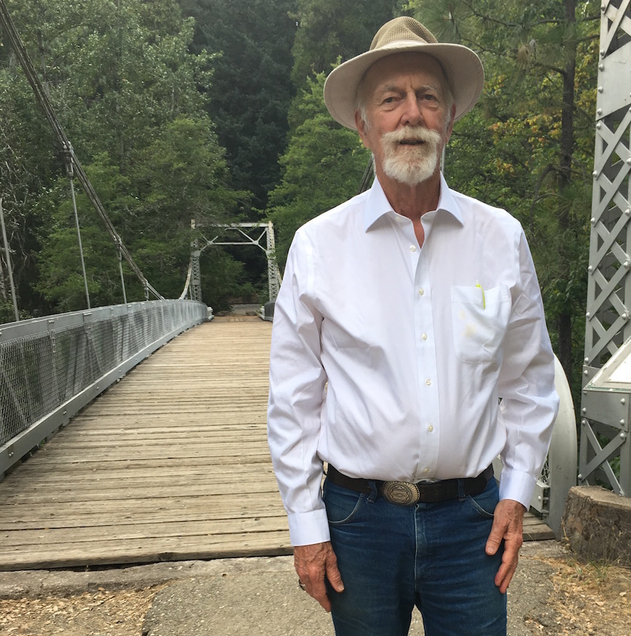 Peter Burke standing on a bridge in the forest